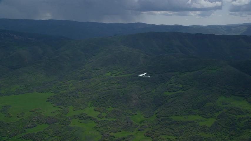 6K stock footage aerial video of tracking Tecnam P2006T airplane near green mountain ridge, Wasatch Range, Utah Aerial Stock Footage   AX140_110