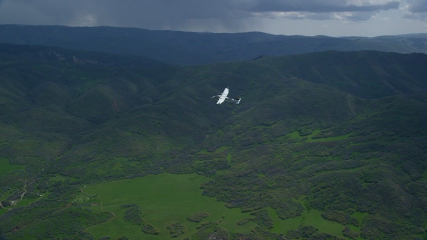 6K stock footage aerial video of tracking Tecnam P2006T near green mountain ridge in the Wasatch Range in Utah Aerial Stock Footage | AX140_111
