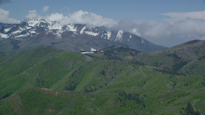 6K stock footage aerial video of tracking Tecnam P2006T near green mountain ridge and snowy peaks, Wasatch Range, Utah Aerial Stock Footage | AX140_113