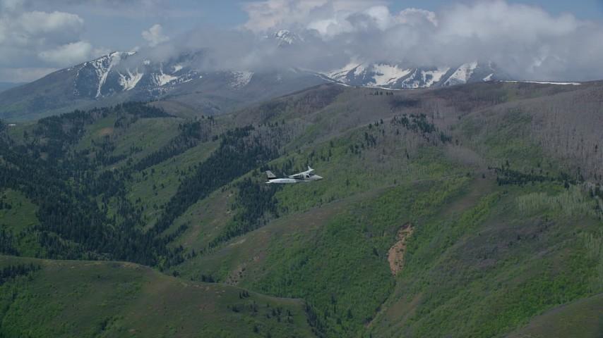 6K stock footage aerial video of a Tecnam P2006T in flight over mountains near snowy peak, Wasatch Range, Utah Aerial Stock Footage | AX140_117