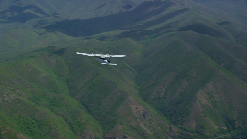6K stock footage aerial video fly around tail of Tecnam P2006T over mountains, revealing Wasatch Range peaks, Utah Aerial Stock Footage | AX140_120