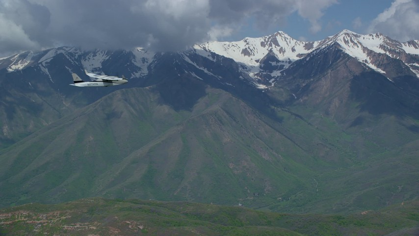 Tracking Tecnam P2006T flying near snowy mountain peak, Wasatch Range, Utah Aerial Stock Footage   AX140_122