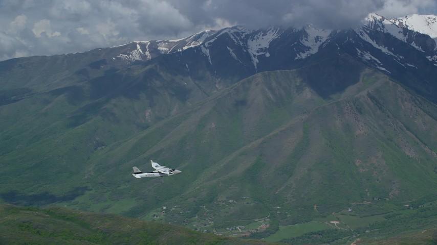 Tracking Tecnam P2006T flying near snowy mountain peak, Wasatch Range, Utah Aerial Stock Footage   AX140_124