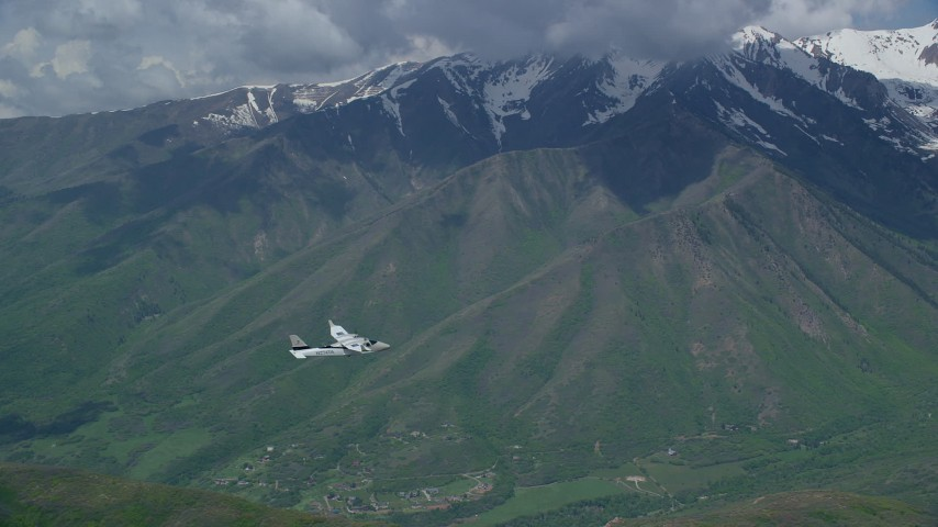 Tracking Tecnam P2006T flying near snowy mountain peak, Wasatch Range, Utah Aerial Stock Footage | AX140_124