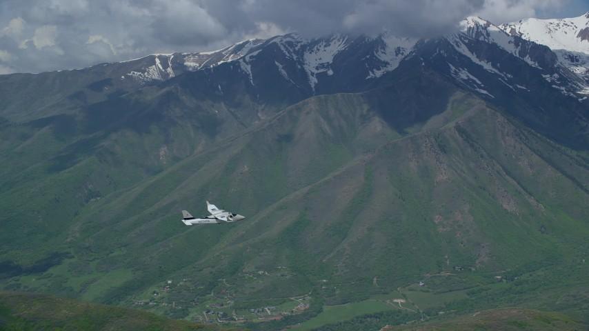 6K stock footage aerial video of tracking a Tecnam P2006T near snowy mountain peak, Wasatch Range, Utah Aerial Stock Footage | AX140_124