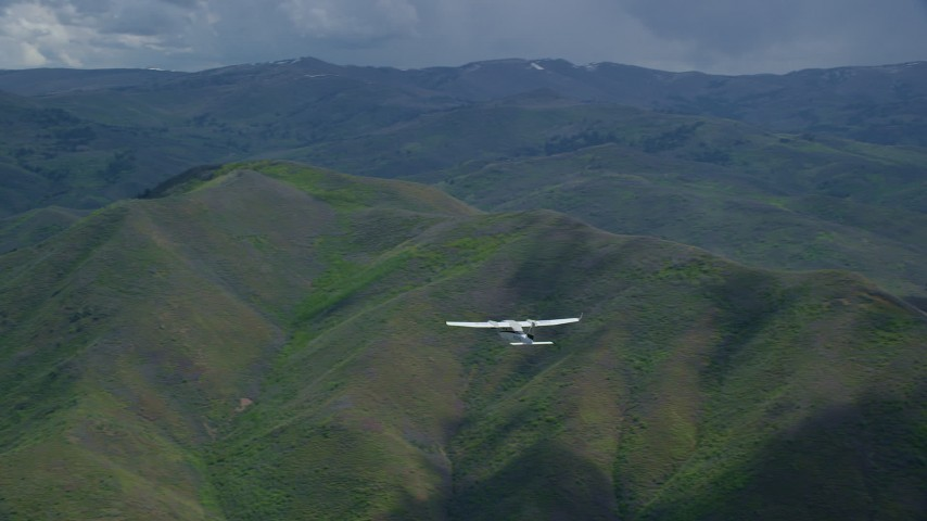 6K stock footage aerial video of tracking Tecnam P2006T in flight over green mountain ridges, Wasatch Range, Utah Aerial Stock Footage | AX140_129