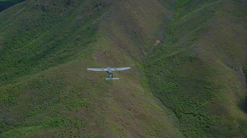 6K stock footage aerial video bird's eye of a Tecnam P2006T aircraft flying over green mountain ridges, Wasatch Range, Utah Aerial Stock Footage | AX140_130