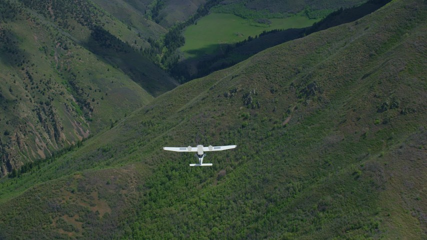 6K stock footage aerial video of a bird's eye of a Tecnam P2006T in flight over green mountain ridges, Wasatch Range, Utah Aerial Stock Footage | AX140_131