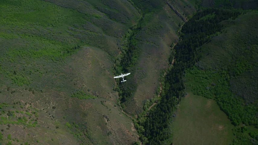 6K stock footage aerial video of a bird's eye of a Tecnam P2006T as it flies over green mountain ridges, Wasatch Range, Utah Aerial Stock Footage | AX140_135