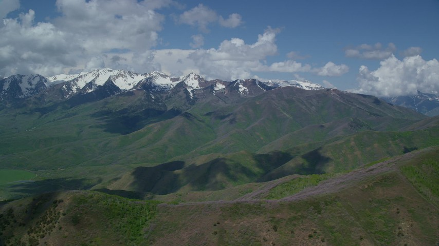 Flying by snow-capped peak, from over green ridges, Wasatch Range, Utah Aerial Stock Footage   AX140_136