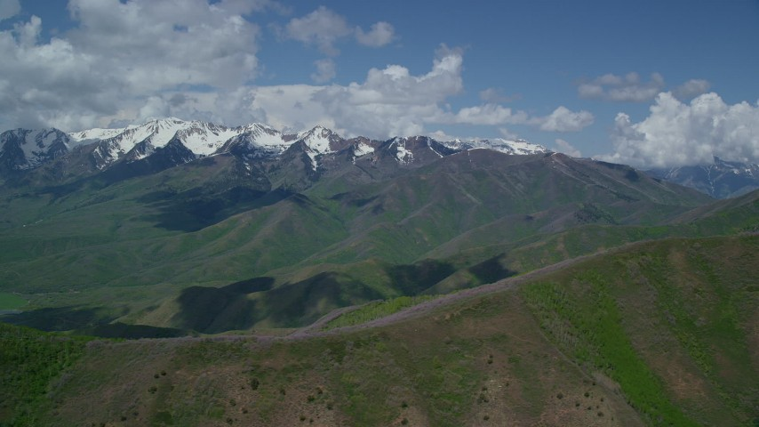 Flying by snow-capped peak, from over green ridges, Wasatch Range, Utah Aerial Stock Footage | AX140_136