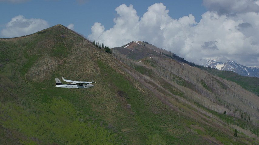 Tecnam P2006T, green mountain, aspen trees, snow patches, Wasatch Range, Utah Aerial Stock Footage | AX140_139