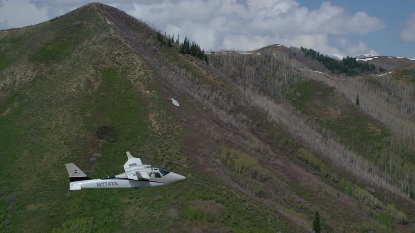 Tecnam P2006T, green mountain, aspen trees, snow patches, Wasatch Range, Utah Aerial Stock Footage | AX140_140