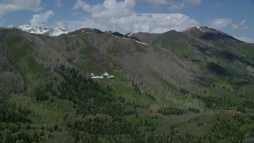6K stock footage aerial video of a Tecnam P2006T passing a green mountain, aspen trees, snow patches, Wasatch Range, Utah Aerial Stock Footage | AX140_141