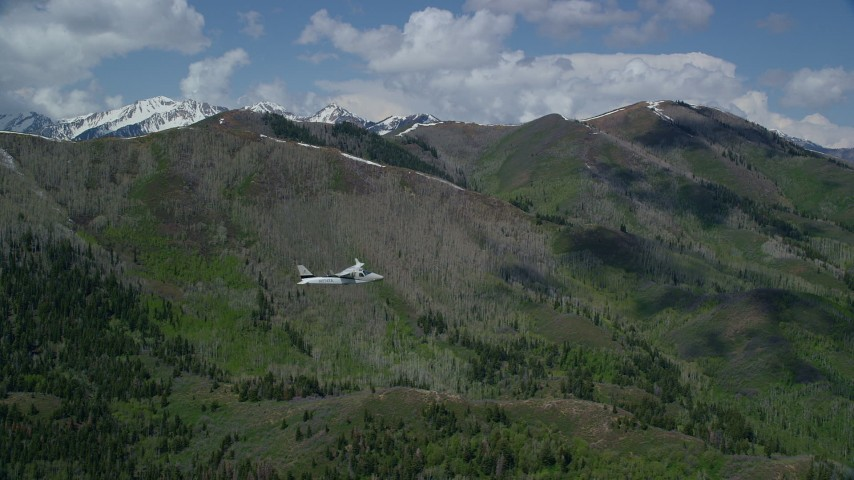 6K stock footage aerial video of a Tecnam P2006T as it passes green mountain, aspen trees, snow patches, Wasatch Range, Utah Aerial Stock Footage | AX140_142