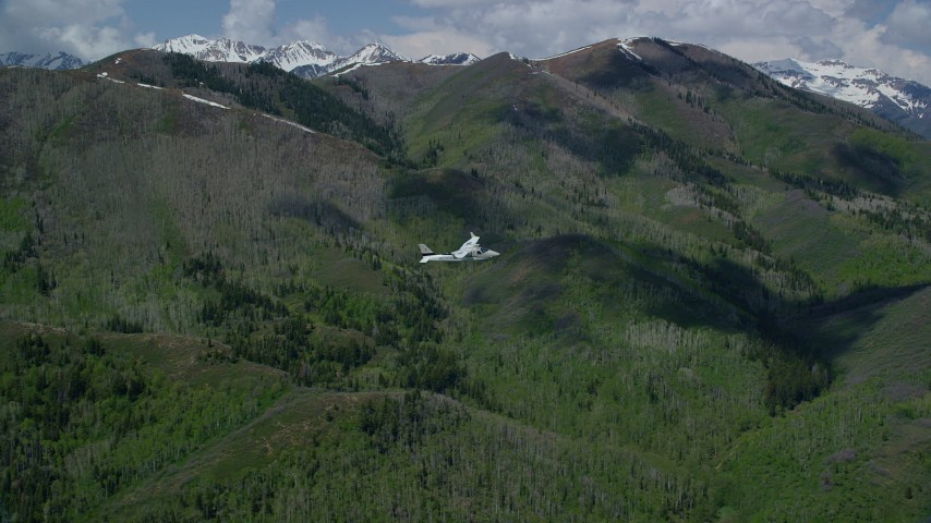 6K stock footage aerial video focus on a Tecnam P2006T passing a green mountain, aspen trees, snow patches, Wasatch Range, Utah Aerial Stock Footage | AX140_143