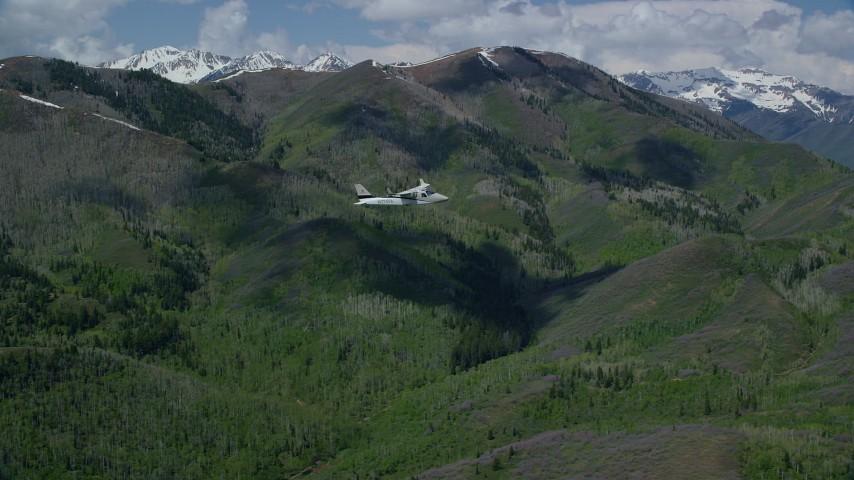 Tecnam P2006T, green mountain, aspen trees, snow patches, Wasatch Range, Utah Aerial Stock Footage | AX140_144