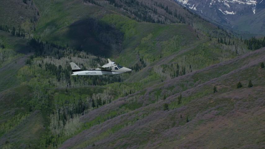Tecnam P2006T by green, purple mountains, aspen trees, Wasatch Range, Utah Aerial Stock Footage   AX140_145