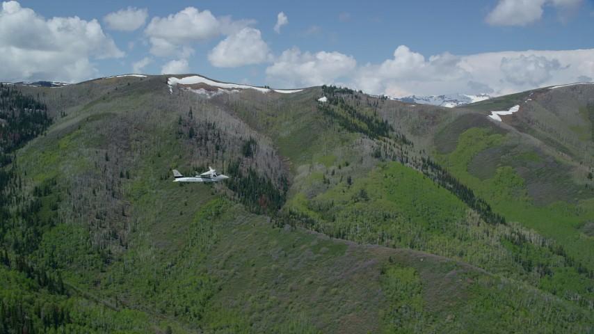 Tecnam P2006T by green, purple mountains, aspen trees, Wasatch Range, Utah Aerial Stock Footage   AX140_148