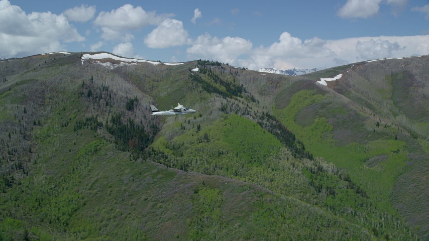 Tecnam P2006T by green, purple mountains, aspen trees, Wasatch Range, Utah Aerial Stock Footage | AX140_148