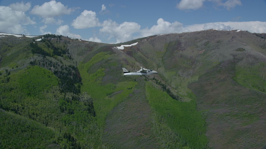 6K stock footage aerial video tracking Tecnam P2006T airplane flying by green and purple mountains, aspen trees, Wasatch Range, Utah Aerial Stock Footage | AX140_149