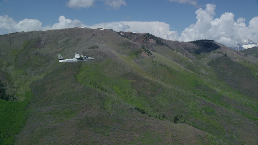 Tecnam P2006T by green mountains, aspen trees, clouds, Wasatch Range, Utah Aerial Stock Footage | AX140_150