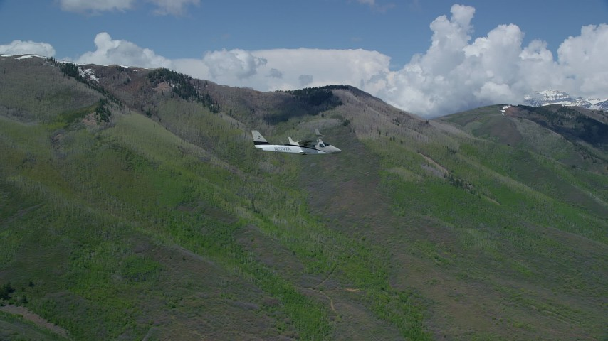 6K stock footage aerial video of tracking a Tecnam P2006T as it flies by green mountains, aspen trees, Wasatch Range, Utah Aerial Stock Footage | AX140_151