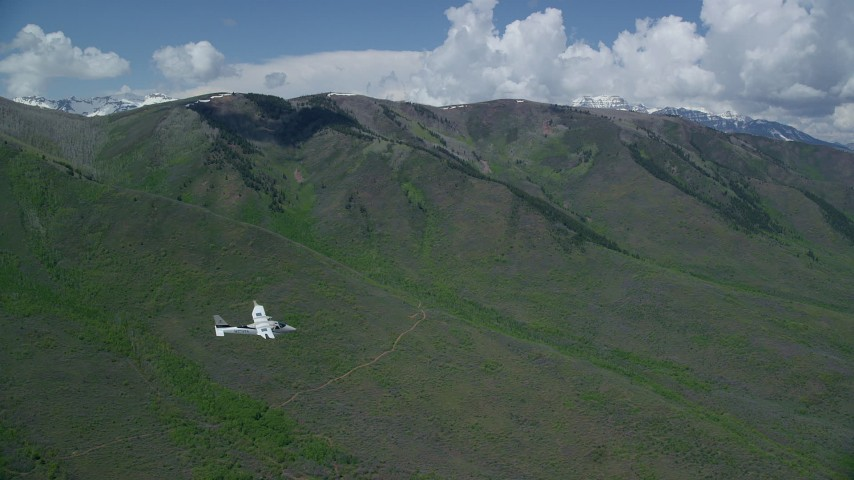 6K stock footage aerial video of a Tecnam P2006T flying by green mountains, Wasatch Range, Utah Aerial Stock Footage | AX140_154