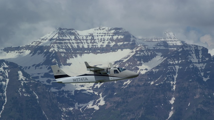 Tracking a Tecnam P2006T flying by snow-capped Mount Timpanogos, Utah Aerial Stock Footage | AX140_161