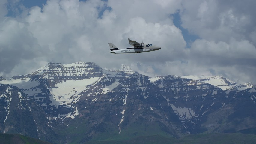 Tracking a Tecnam P2006T flying by snow-capped Mount Timpanogos, Utah Aerial Stock Footage | AX140_162