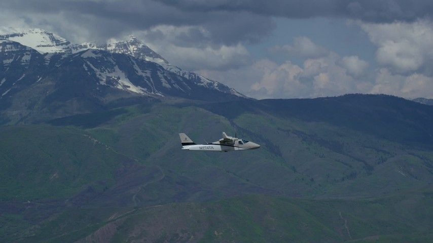 Tracking a Tecnam P2006T flying by snow-capped Mount Timpanogos, Utah Aerial Stock Footage | AX140_163