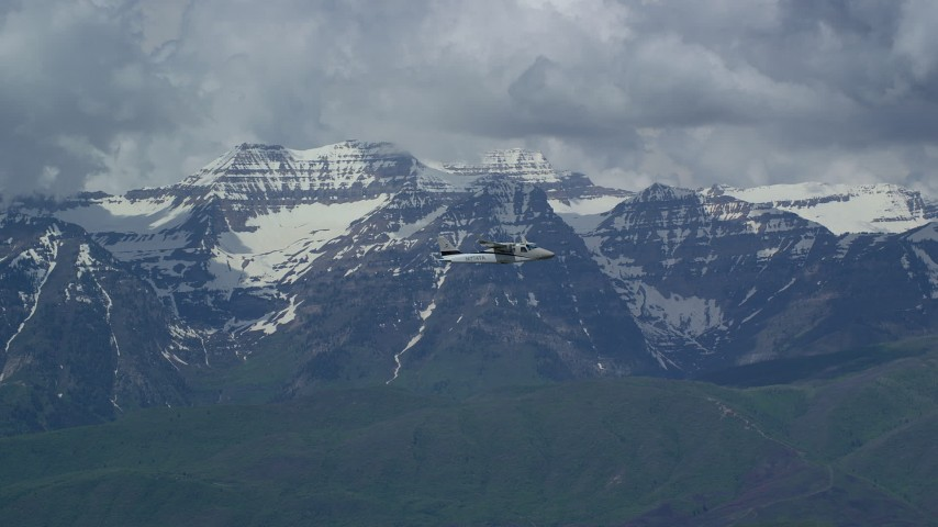 Tracking Tecnam P2006T flying by snow-capped Mount Timpanogos, Utah Aerial Stock Footage | AX140_167