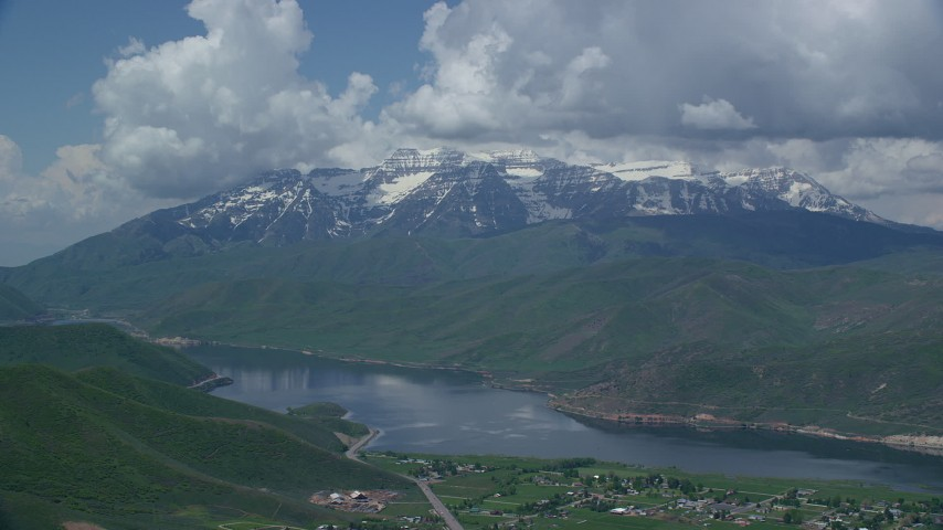 6K stock footage aerial video of Deer Creek Reservoir. with snow-capped Mount Timpanogos in the distance, Utah Aerial Stock Footage | AX140_174