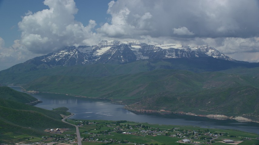 Flying by Deer Creek Reservoir, homes, snow-capped Mount Timpanogos, Utah Aerial Stock Footage | AX140_175