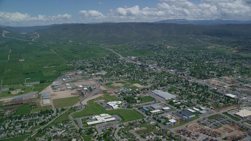 Approaching small town, neighborhoods, pan right, Heber City, Utah Aerial Stock Footage | AX140_176