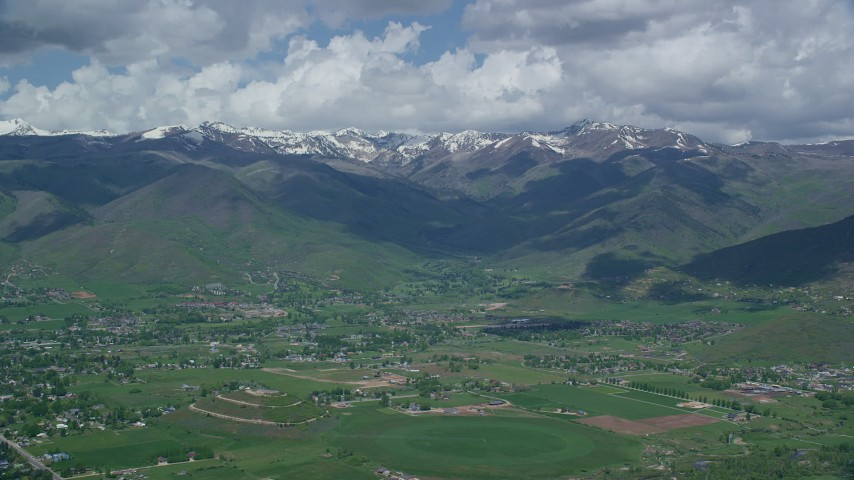 Flying by snowy peaks from over small town of Midway, Wasatch Range, Utah Aerial Stock Footage | AX140_179