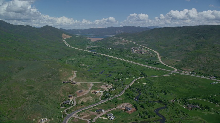 6K stock footage aerial video of flying by Highway 40 through green mountain foothills and homes, Heber City, Utah Aerial Stock Footage | AX140_185
