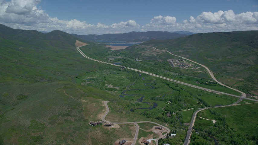 6K stock footage aerial video of a view of Highway 40 through green mountain foothills, Heber City, Utah Aerial Stock Footage   AX140_186