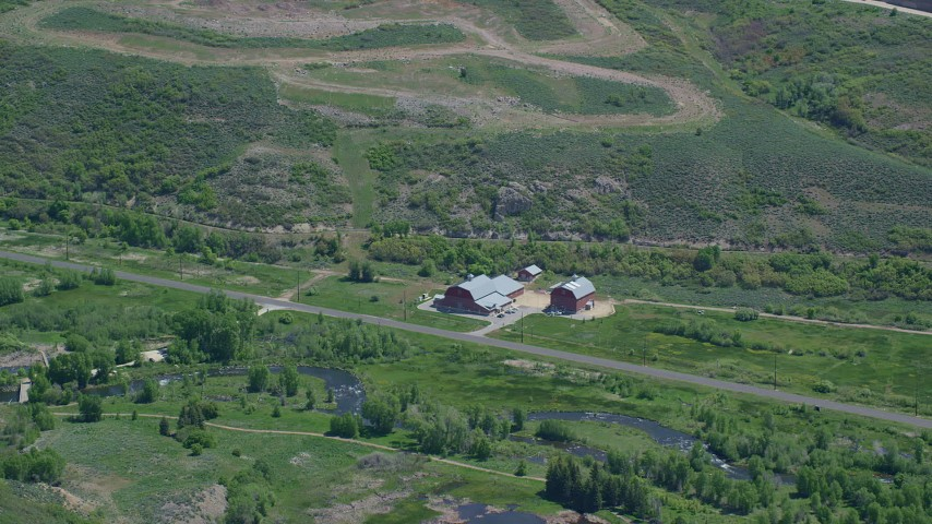 6K stock footage aerial video of flying by large barns near Old Highway 40 and a river, Heber City, Utah Aerial Stock Footage | AX140_189
