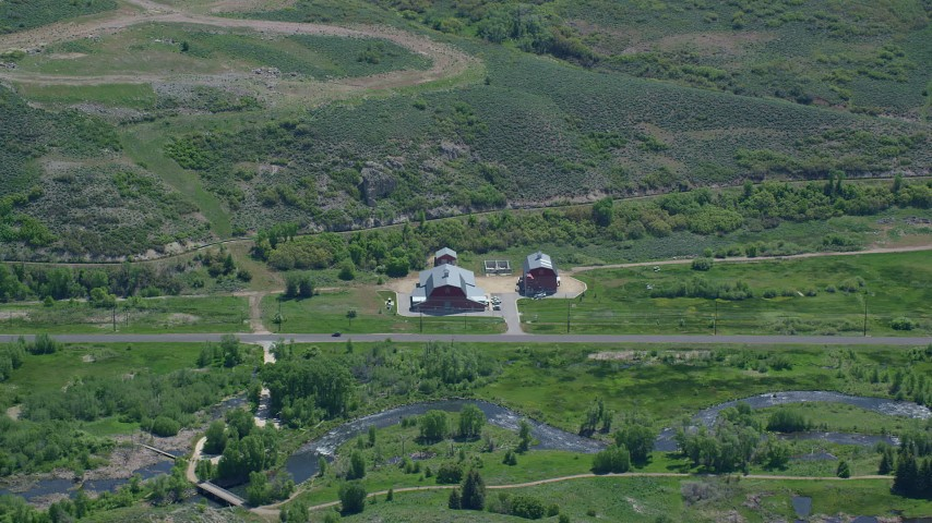 Flying by large barns near Old Highway 40, river, Heber City, Utah Aerial Stock Footage | AX140_190