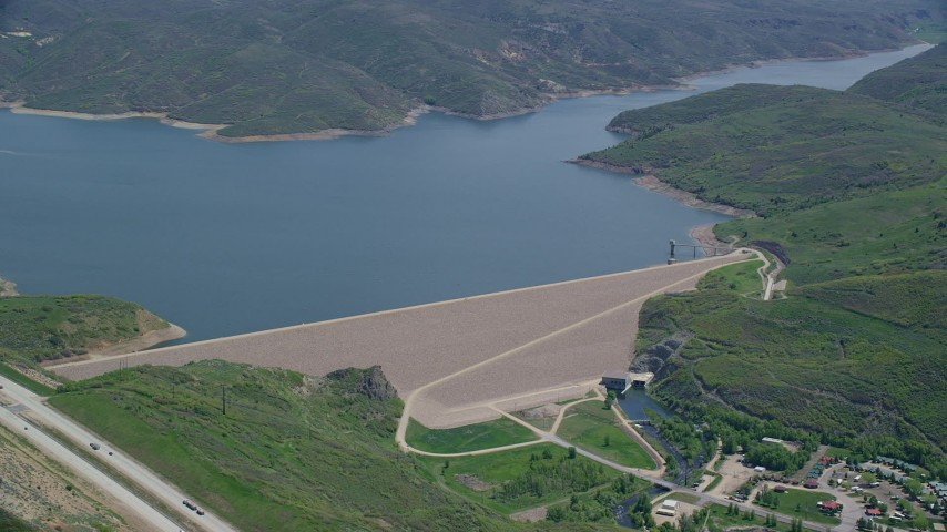 6K stock footage aerial video of a dam surrounded by green hills, reveal the highway, Jordanelle Dam, Utah Aerial Stock Footage | AX140_191
