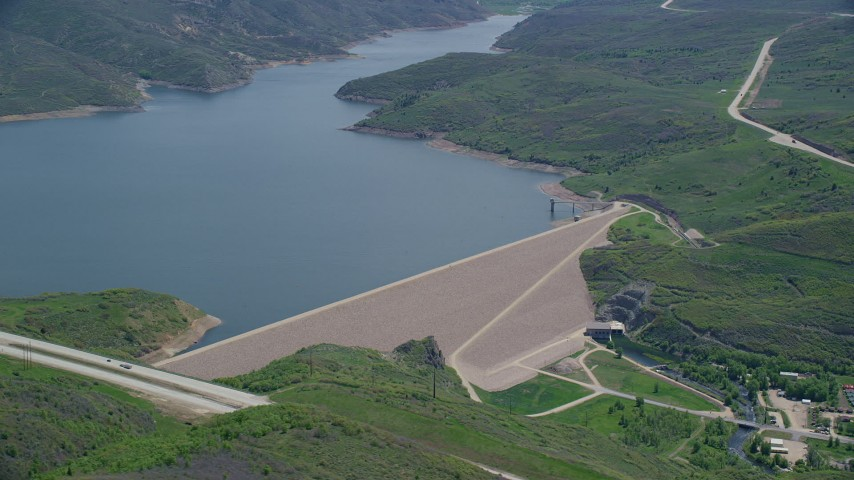 Flying by dam surrounded by green hills, revealing highway, Jordanelle Dam, Utah Aerial Stock Footage | AX140_192