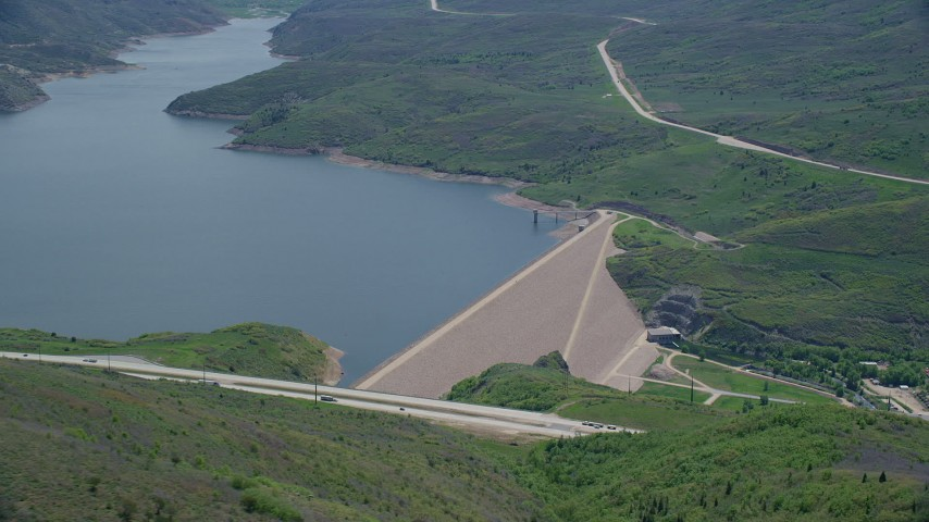 6K stock footage aerial video of circling dam beside a highway, Jordanelle Dam, Utah Aerial Stock Footage | AX140_193