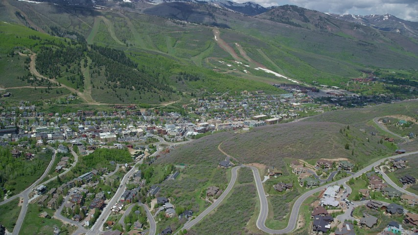 6K stock footage aerial video of flying over condos to approach town center, green mountains, Park City, Utah Aerial Stock Footage | AX140_201