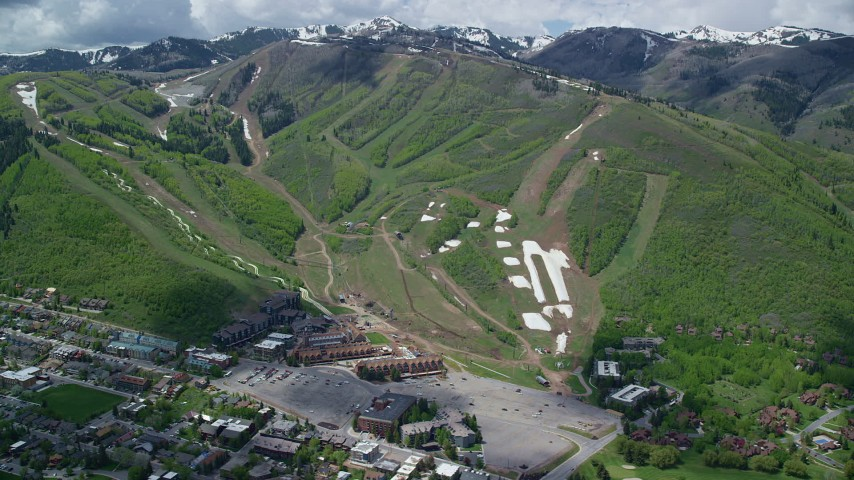 6K stock footage aerial video of Park City Mountain Resort, green slopes and distant snowy peaks, Park City, Utah Aerial Stock Footage | AX140_204