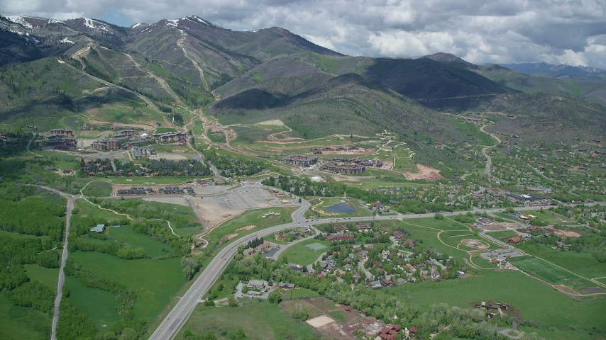 6K stock footage aerial video of flying by Canyons Resort near snowy mountain peaks, Park City, Utah Aerial Stock Footage | AX140_208
