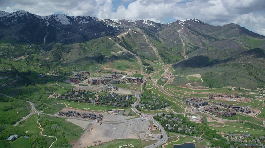 6K stock footage aerial video of Canyons Resort, with view of snowy mountain peaks, Park City, Utah Aerial Stock Footage AX140_209 | Axiom Images