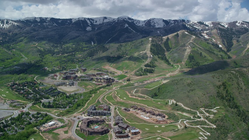 6K stock footage aerial video of flying by Canyons Resort with snowy mountain peaks in the background, Park City, Utah Aerial Stock Footage | AX140_211