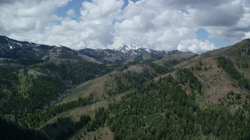 6K stock footage aerial video of passing by green mountains, snowy peaks in the distance, Wasatch Range, Utah Aerial Stock Footage | AX140_226