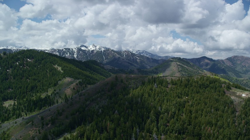 Flying by green mountains, snowy peaks in the distance, Wasatch Range, Utah Aerial Stock Footage | AX140_229